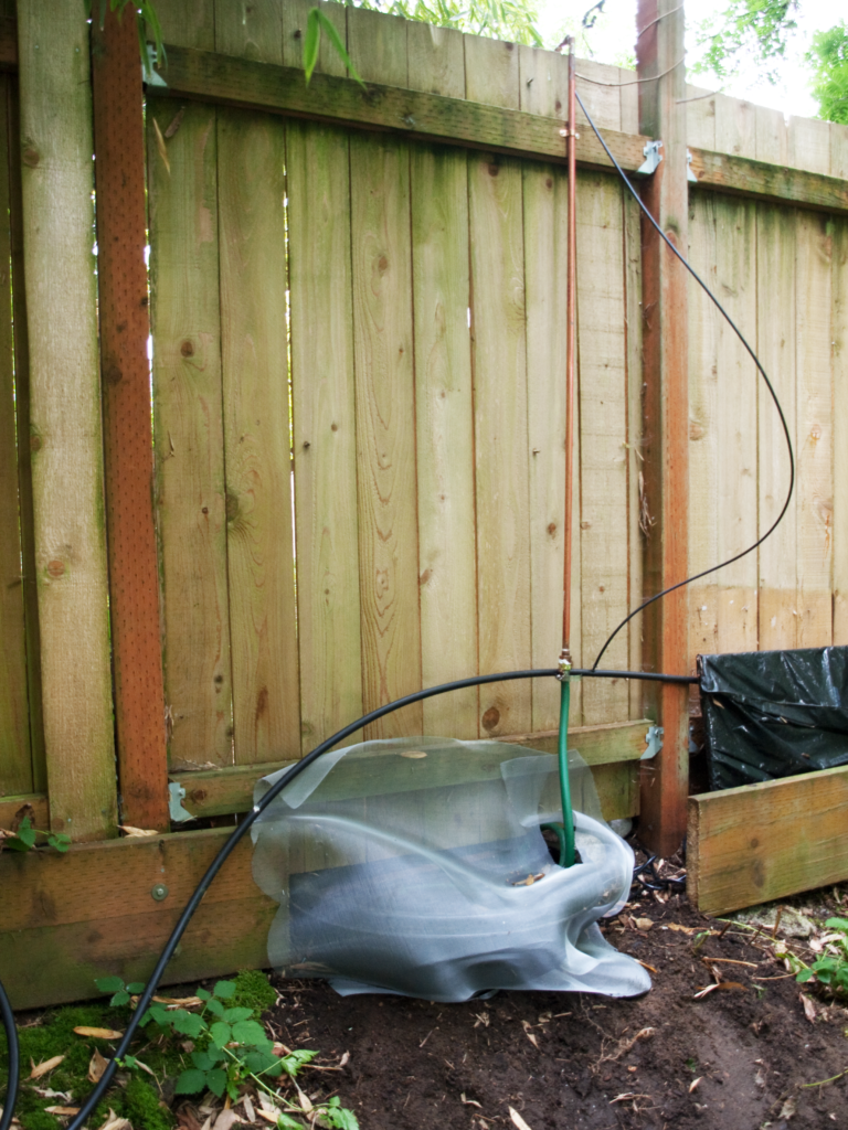 Photo of backside of fence of the DIY Waterfall Feature For Backyard Fence